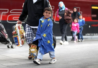 MUNICH, GERMANY - SEPTEMBER 05: A migrant boy covered in a EU flag arrives from Austia at Munich Hauptbahnhof main railway station on September 5, 2015 in Munich, Germany. Thousands of migrants are traveling to Germany following an arduous ordeal in Hungary that resulted in thousands walking on foot and then being bussed by Hungarian authorities from Budapest to the Austrian-Hungarian border. (Photo by Alexandra Beier/Getty Images)