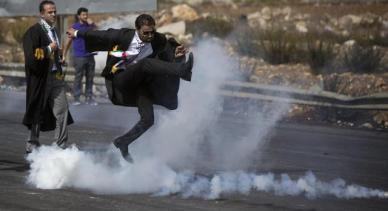A lawyer wearing his official robes kicks a tear gas canister back toward Israeli soldiers during a demonstration by scores of Palestinian lawyers called for by the Palestinian Bar Association in solidarity with protesters at the Al-Aqsa mosque compound in Jerusalem's Old City, near Ramallah, West Bank, Monday, Oct. 12, 2015. In recent weeks, at least 25 Palestinians, including nine attackers, have been killed by Israeli forces, while five Israelis have been killed in attacks. (ANSA/AP Photo/Majdi Mohammed)
